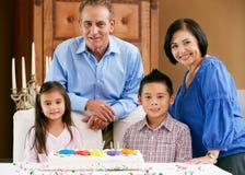 Abuelos que celebran la torta del cumpleaños de los niños Fotos de archivo libres de regalías