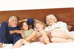 Abuelos que cosquillean a nietos en cama Imagenes de archivo