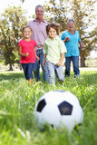 Abuelos que juegan al balompié con los nietos Fotografía de archivo