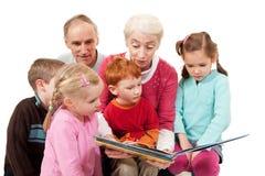 Abuelos que leen el libro de la historia de los cabritos a los niños Imagen de archivo