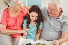 Abuelos que leen un libro con la nieta Imagen de archivo libre de regalías