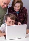 Abuelos que muestran adolescentes cómo utilizar el ordenador Imagen de archivo libre de regalías