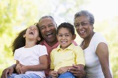 Abuelos que ríen con los nietos Foto de archivo