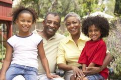 Abuelos que se relajan en jardín con los nietos Fotografía de archivo libre de regalías
