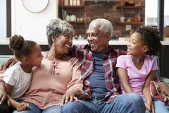 Abuelos que se relajan en Sofa At Home With Granddaughters imágenes de archivo libres de regalías