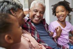 Abuelos que se relajan en Sofa At Home With Granddaughters imagen de archivo libre de regalías