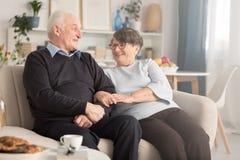 Abuelos que se sientan en el sofá foto de archivo libre de regalías