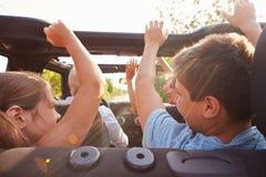 Abuelos que toman a nietos en viaje en coche de tragante abierto Imágenes de archivo libres de regalías