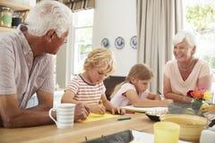 Abuelos sonrientes con los grandkids en la cocina, cierre para arriba fotos de archivo libres de regalías