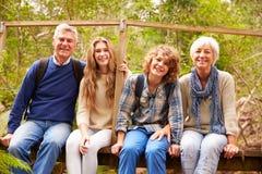 Abuelos y adolescencias que se sientan en un puente en un bosque Imagenes de archivo