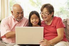 Abuelos y Grandaughter usando cálculo de la computadora portátil Fotografía de archivo