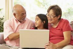 Abuelos y Grandaughter usando cálculo de la computadora portátil Fotos de archivo