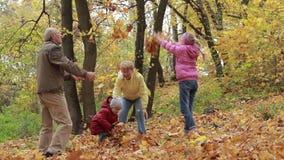 Abuelos y niños que se divierten en parque del otoño almacen de video