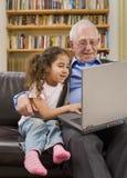Abuelos y nieta con el ordenador Fotos de archivo libres de regalías