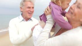 Abuelos y nieta que caminan a lo largo de la playa junto