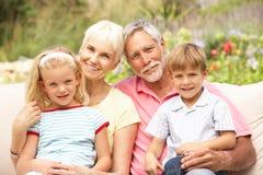 Abuelos y nietos que se relajan en jardín imágenes de archivo libres de regalías