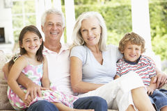 Abuelos y nietos que se sientan en Cane Sofa At Home fotos de archivo