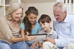 Abuelos y ordenador de la tablilla de los nietos Fotografía de archivo