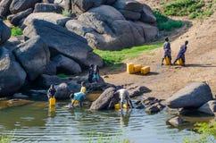 Abuja, Nigeria - Maart 13, 2014: Niet geïdentificeerde jonge kinderen die gele watercontainers vullen bij rivier Stock Afbeelding