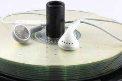 Abultan los Cdes y los auriculares Imagen de archivo libre de regalías