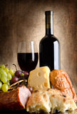 Abundance. Wine, cheese, grapes and sausage on an old canvas Royalty Free Stock Photos