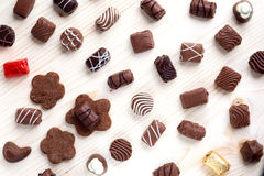 Abundance of chocolates on a light wooden background close up Royalty Free Stock Photos