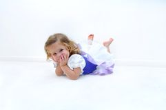 Abundance of Energy. A tired little ballerina lays on the floor in an all white room.  She is dressed in a ballerina costume of lilac and purple.  Child is Stock Image
