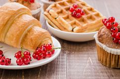 Abundance of pastries decorated with red currant/abundance of pastries decorated with red currant on a wooden background. Selective focus dessert cake wafers royalty free stock photography