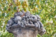 Abundance of sculptural fruits on a heavenly stone dish. Autumn in Spain. Abundance of sculptural fruits on a heavenly stone dish in the autumn Park, garden stock photos