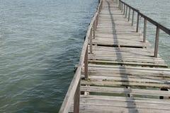 Abundance wooden jetty. Old broken abundance wooden jetty leading toward ocean Stock Photo