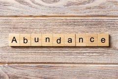 Abundance word written on wood block. abundance text on table, concept.  stock image