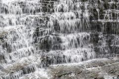 Abundant waterfall flowing of cascading rock in many small tiers. Refreshing relaxing scene depicting motion Royalty Free Stock Photo