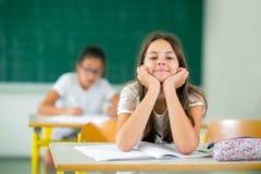 Aburren a la niña en la sala de clase imagenes de archivo