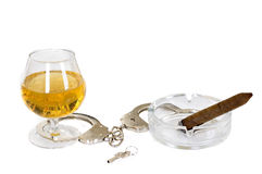 Abuse. Glass with alcohol, ashtray with cigar and handcuffs isolated on white background Stock Photography