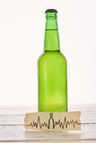 Abuse of alcohol harmful for heart. Image of cardiac impulses, bottle of beer Stock Photo