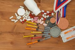 Abuse of anabolic steroids for sports. Anabolic steroids spilled on a wooden table. Fraud in sports. Pharmaceutical industry. Detailed view of the medication stock photography