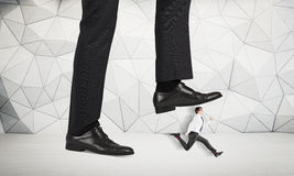 Abuse of authority. Concept with huge businessman foot stepping on a running male miniature with patterned concrete wall in the background stock images
