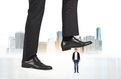 Abuse of authority NY. Abuse of authority concept with huge businessman foot stepping on a male miniature on New York city background stock photo