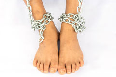 Abused Boy. Sitting on the Floor with Chain on Foot, Leaning his Head and Arms on Knees with holding chain Stock Image