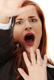 Abused businesswoman. Scared abused businesswoman trying to defend herself Royalty Free Stock Photos