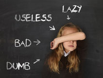 Abused disciplined schoolgirl pointed as lazy dumb bad and useless on class blackboard. Little beautiful blond schoolgirl sad ashamed and embarrassed being royalty free stock photography