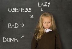 Abused disciplined schoolgirl pointed as lazy dumb bad and useless on class blackboard Stock Images