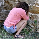 Abused and frightened woman sitting in the corner of a derelict. Building Stock Images