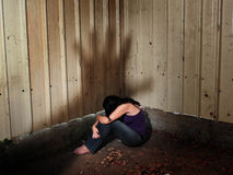 Abused Victim. A woman who is a victim of abuse is hiding in the darkness of an old shed, sitting on the ground with a shadow of a mans hand hovering over her stock photos