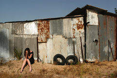 Abused Victim. A woman who is a victim of abuse is sitting on outside an old shed sad and depressed Stock Image