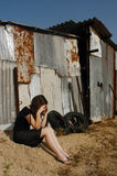 Abused Victim. A woman who is a victim of abuse is sitting on outside an old shed sad and depressed Royalty Free Stock Photography