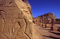AbuSimbel slave wall. Stone wall on left side coming out of AbuSimbel temple royalty free stock photos