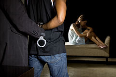 Abusive Man Being Arrested for Domestic Violence. Cop arresting a men for domestic violence and female victim in the background Royalty Free Stock Images