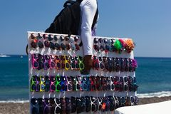 Abusive sells counterfeit sunglasses on Kamari beach. Royalty Free Stock Image