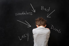 Abusive words hurt. A young boy sits in front of a blackboard that has abusive words written in chalk stock images